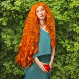 Young redhead princess with very long hair in blue dress on a green summer background. A beautiful woman with pale skin, red lips Royalty Free Stock Photography