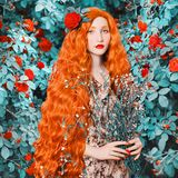 Young redhead renaissance woman in flower dress on rose background. A beautiful girl with pale skin, red lips and blue eyes. Renaissance princess in a spring stock photography