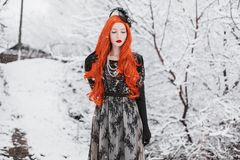 Young redhead retro girl with long red hair on winter background. Awesome winter snow fall. Redhead woman in black retro dress and royalty free stock images