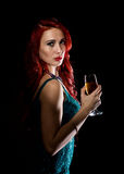 Young redhead sexy woman in blue elegant dress holding wineglass with champagne and poses in a dark. Young redhead sexy woman in blue elegant dress holding Stock Image
