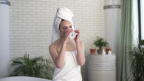 Young redhead smiling woman drinks from a glass and listens to music in the bath stock footage