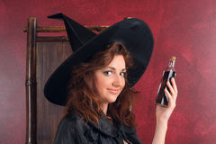 Young redhead witch with potions Stock Images