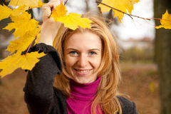 Young redhead woman with autumn leaves. Looking at the camera stock images