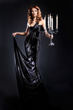 A young redhead woman in a dark long dress. A young and attractive redhead Caucasian woman posing in a dark long dress and holding candles. The image is taken on Stock Photos