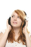 Young redhead woman is daydreaming while listening Stock Photos