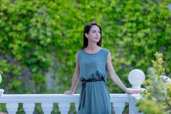 Young redhead woman in dress standing in garden, stock photo