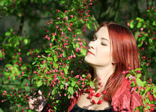 Young redhead woman enjoying cherry blossom Stock Photos