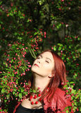 Young redhead woman enjoying cherry blossom in the sunshi Royalty Free Stock Photography