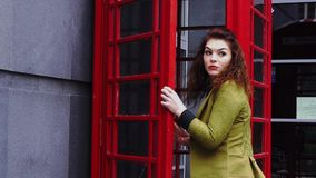 Young redhead woman entering telephone booth stock video