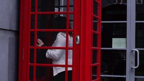 Young redhead woman entering telephone booth stock video footage