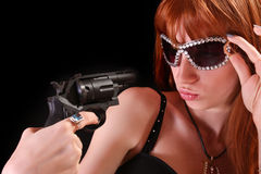 Young redhead woman and gun to her face Stock Images