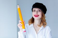 Young redhead woman in hat holding chuge pencil Stock Photo
