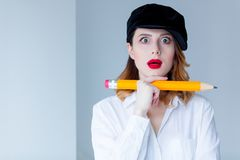 Young redhead woman in hat holding chuge pencil Royalty Free Stock Photos
