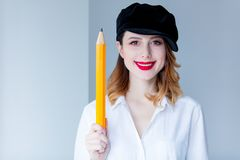 Young redhead woman in hat holding chuge pencil Royalty Free Stock Images