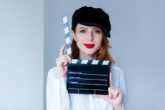 Young redhead woman in hat holding movie clapboard. On grey background Stock Images