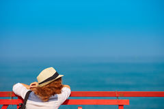 Young redhead woman in hat on pier looks out into ocean Stock Image