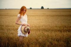 Young redhead woman with hat standing in a wheat field Royalty Free Stock Images