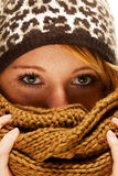 Young redhead woman hiding behind scarf Royalty Free Stock Images