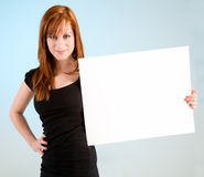 Young Redhead Woman Holding a Blank White Sign. A beautiful young redhead woman is holding a blank white sign stock image