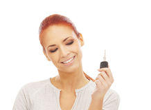 A young redhead woman holding a car key Royalty Free Stock Images