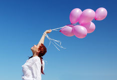 Young redhead woman. Holding pink balloons royalty free stock photo