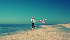 Young redhead woman. Holding pink balloons stock photo
