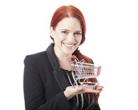 Young redhead woman holding a shopping cart Royalty Free Stock Image