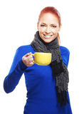 A young redhead woman holding a yellow mug Royalty Free Stock Photos
