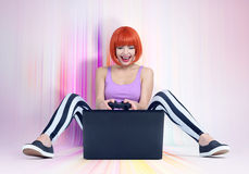 Young redhead woman with joystick sits on the multicolored floor in front of a laptop. Gamer plays. Royalty Free Stock Images