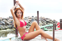 A young redhead woman laying in a pink swimsuit Royalty Free Stock Image