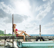 A young redhead woman laying in a pink swimsuit Stock Photography