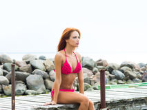 A young redhead woman laying in a pink swimsuit Stock Images