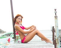 A young redhead woman laying in a pink swimsuit Royalty Free Stock Photography
