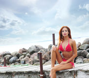 A young redhead woman laying in a pink swimsuit Stock Photos
