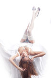 A young redhead woman laying in white lingerie Stock Photo