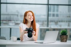 Redhead woman looking at camera while working on laptop. Young redhead woman looking at camera while working on laptop. Photographer with her camera and laptop Stock Images
