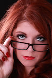 Young redhead woman looking over glasses on nose. Young redhead woman with questioning look over glasses Stock Photography