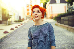 Young redhead woman looking up standing on the urban street Royalty Free Stock Image