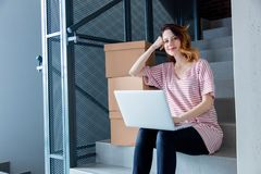 Young redhead woman with moving boxes and laptop. Sitting on stairs in house. European ethnicity Royalty Free Stock Photos