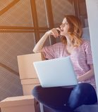 Young redhead woman with moving boxes and laptop. Sitting on stairs in house. European ethnicity Stock Photos