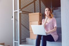 Young redhead woman with moving boxes and laptop. Sitting on stairs in house. European ethnicity Stock Image