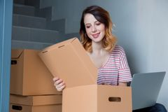 Young redhead woman with moving boxes and laptop. Sitting on stairs in house. European ethnicity Stock Photography