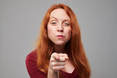 Young redhead woman pointing with an index finger at yo Royalty Free Stock Photos