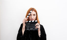Young redhead woman portrait with black movie clapper board Stock Photos