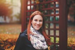 Young redhead woman portrait smiling in park at autumn. Young caucasian redhead woman portrait smiling in park at autumn Royalty Free Stock Photo
