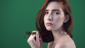 Young redhead woman posing on camera. Looking on hair tips. stock video