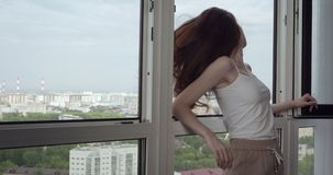 Young woman posing near open window at home. stock footage