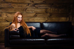Young redhead woman posing on the sofa Stock Photos