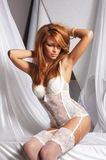 A young redhead woman posing in white lingerie Royalty Free Stock Photos