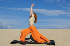 Young redhead woman practicing warrior pose from yoga on the bea Royalty Free Stock Image